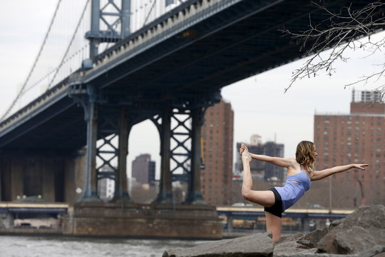 A woman strikes a yoga pose at the Brooklyn Bridge Park in New York