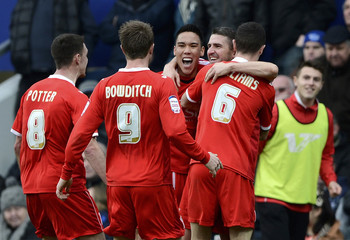 Milton Keynes Dons' Lowe celebrates with team mates after scoring against Queens Park Rangers during their English FA Cup fourth round soccer match at Loftus Road in London