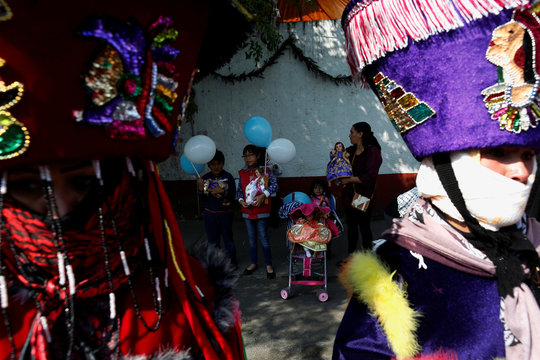 A woman and children are carrying dressed-up dolls representing baby Jesus between Chinelo costumed dancers during the Feast of Candelaria celebration, where elaborate effigies of young Jesus are carried to be blessed 40 days after his birth, in Xochimilc