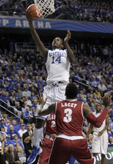 University of Kentucky's Michael Kidd-Gilchrist shoots under pressure from University of Alabama's Trevor Lacey during the first half of play in their NCAA basketball game at Rupp Arena in Lexington