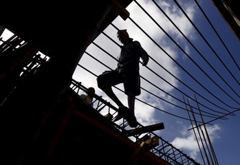 A labourer walks on an iron frame at the construction site of a residential complex on the outskirts of Kolkata