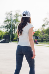 Pretty young woman in the park with her back turned