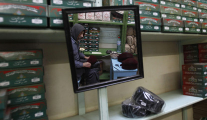 A craftsman who specialises in the production of traditional chechia caps  is reflected in a mirror cba3d276f