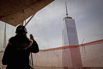 A woman uses her phone to photograph One World Trade Center from one of the top floors of the newly built 30 Park Place in the Tribeca neighborhood of New York