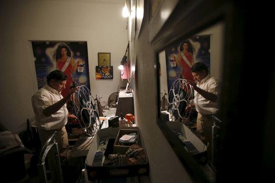 Projectionist Antonio Feliciano spools film onto projection reels at Girasol cinema in Vila Nova de Milfontes
