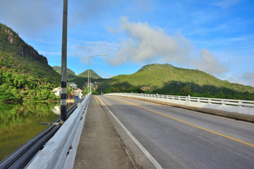 .Bridge heading to mountains with blue sky background in Thailand.