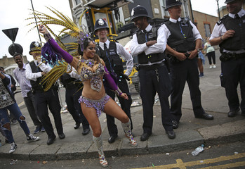 Police look as a performer dances during the Notting Hill Carnival in London