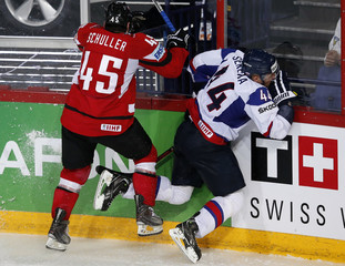 Austria's Schuller and Slovakia's Sekera collide into the glass during their 2013 IIHF Ice Hockey World Championship preliminary round match at the Hartwall Arena in Helsinki