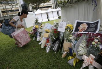 A woman places flowers in tribute to the late former prime minister Lee Kuan Yew outside the Parliament House in Singapore