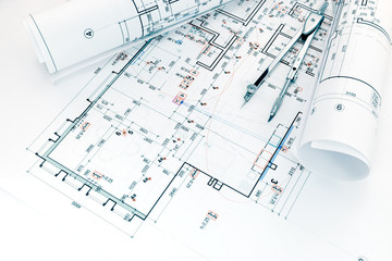 architects workplace with project plans of house arrangement and drawing compass