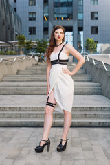 Young beautiful sexy woman wearing trendy outfit, white dress and leather swordbelt. Longhaired brunette posing in the city street. Outdoor fashion photography
