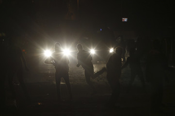 Protesters, who oppose Egyptian President Mohamed Mursi, flee from riot police during clashes in Cairo