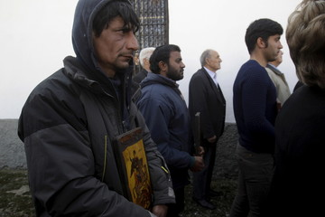 Christian Orthodox Syrian refugee Abdul Selam, who has been living for five days at a makeshift camp for refugees and migrants, holds an icon during a mass marking the Sunday of Orthodoxy at the church of the village of Idomeni