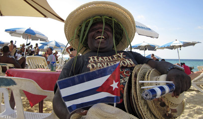 Michel, a retired merchant ship sailor, waits for customers to buy hats with the Cuban flag on a beach on the outskirts of Havana
