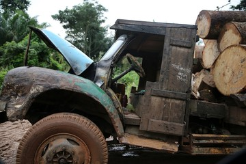 A truck with a wooden cabin sits trapped on a muddy road leading to an unreserved forest in Igbatoro village