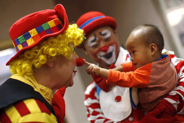 Showichi Hashimoto pushes on the nose of Diana Ciepiela as he is held by his father Junji at the World Clown Association's annual convention in Northbrook