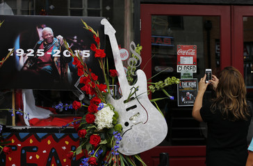 A woman takes a photo of the closed sign next to a small memorial set up in front of the B.B. King Blues Club in Memphis