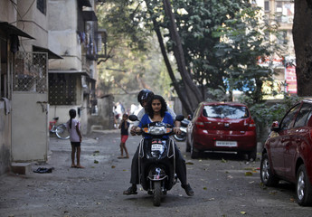 Makwana teaches his daughter Mansi how to ride a scooter at a residential area in Mumbai