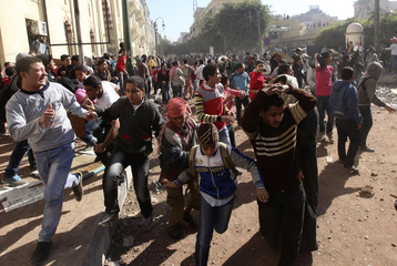 Protesters run during clashes with army soldiers next to a building near cabinet offices near Tahrir Square in Cairo