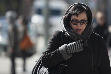 A woman huddles under her coat as she makes her way through the cold in New York