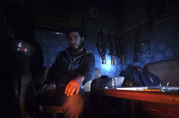 A Free Syrian Fighter rests in a safehouse in the besieged area of Homs