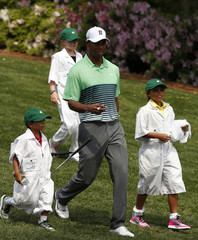 U.S. golfer Tiger Woods walks with his children Charlie and Sam during the par 3 event held ahead of the 2015 Masters at Augusta National Golf Course in Augusta