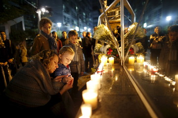 Mother lights up a candle with her child as they pay tribute to the victims of Paris attacks in front of the French embassy in Seoul