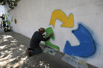 An activist paints a recycling symbol on a wall along the streets of Guatemala City