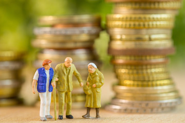 Retire figurine elderly man and women take care and welcome by nursing home with coin stack