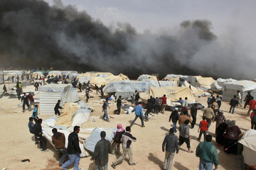 Jordanian firefighters and Syrian refugees try to remove tents before they are damaged by a fire at Al Zaatari