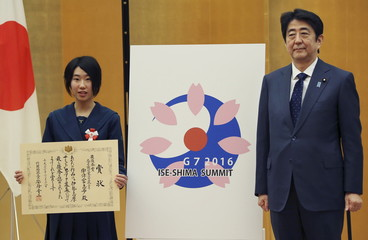 Japanese Prime Minister Shinzo Abe (R) and high school student Shiho Utsumiya pose with her design for the logo of the Ise-Shima G7 summit at the prime minister's official residence in Tokyo
