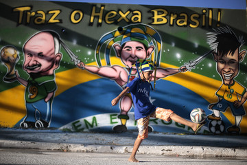 A boy plays soccer in a street decorated with graffiti of Brazil's national soccer players, referencing the 2014 World Cup, in the neighborhood of Ceilandia