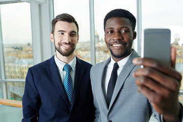 Portrait of handsome bearded businessman and his African partner taking smartphone selfie smiling to camera