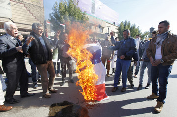 Iraqis set fire to a French national flag during a demonstration against the satirical French weekly Charlie Hebdo's cartoons of the Prophet Mohammad, in Baghdad
