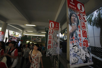 """People walk past campaign banners of pro-democracy lawmaker """"Long Hair"""" Leung Kwok-hung, from League of Social Democrats, for the Legislative Council election campaign in Hong Kong"""