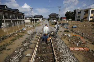 Local residents walk along a railway at a residential area flooded by the Kinugawa river, caused by typhoon Etau, at Mitsukaido district in Joso