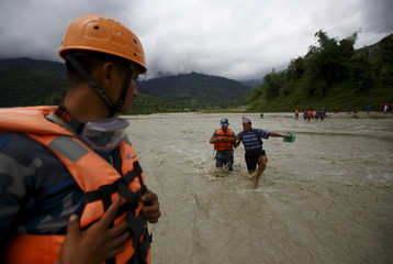 A rescue team member helps a villager to cross a flooded river after the trail bridge was washed away due to heavy rainfall in Kaski