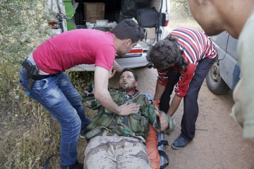 An injured rebel fighter from 'Jaysh al-Sunna' is being helped during what they said was an offensive to take control of al-Mastouma military camp which is controlled by forces loyal to Syria's President Bashar al-Assad beside Idlib city