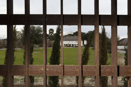 The main house of the Whitney Plantation is seen through the bars of a steel cage used as a jail in Wallace Louisiana