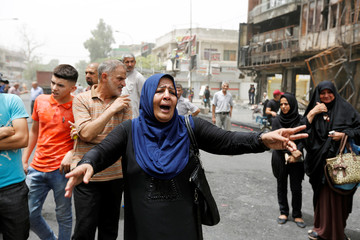 A woman reacts at the site after a suicide car bomb attack at the shopping area of Karrada, a largely Shi'ite district, in Baghdad