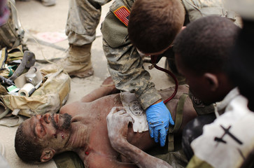 Rico Dibrivell, 35, is attended to by a U.S. military rescue team after being freed from the rubble of a building in Port-au-Prince