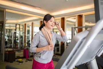 Asian woman running with machine walking