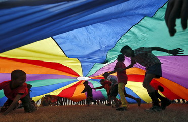 Children play under a parachute shaped cloth installed by a non-governmental organisation for the New Year celebrations at a public park in Kolkata