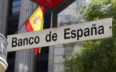 A Spanish flag flies near a Bank of Spain metro sign in central Madrid