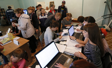 People, who have fled the fighting in the eastern regions of Ukraine, queue for job vacancies at an employment fair at the dormitories where they have taken refuge in Krasnoyarsk