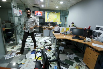 File photo of an employee walking on newspapers after protesters attacked office of Saudi-owned newspaper Asharq al-Awsat in Beirut