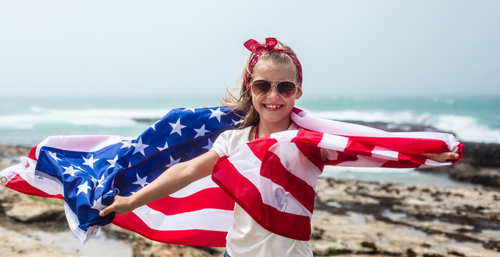 American flag. Little smiling  patriotic girl with long blond hair holding American flag on Independence day USA, July 4th. Memorial day