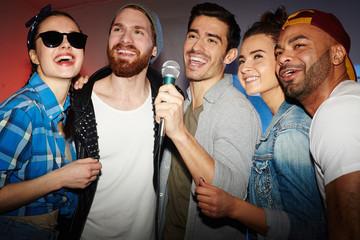 Group of buddies singing karaoke in club