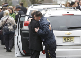 People embrace as they leave the funeral services for Noah Pozner, the youngest victim of the Sandy Hook Elementary School shooting, in Fairfield, Connecticut