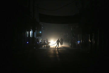 Residents walk at night on New Year's Eve in eastern al-Ghouta, near Damascus